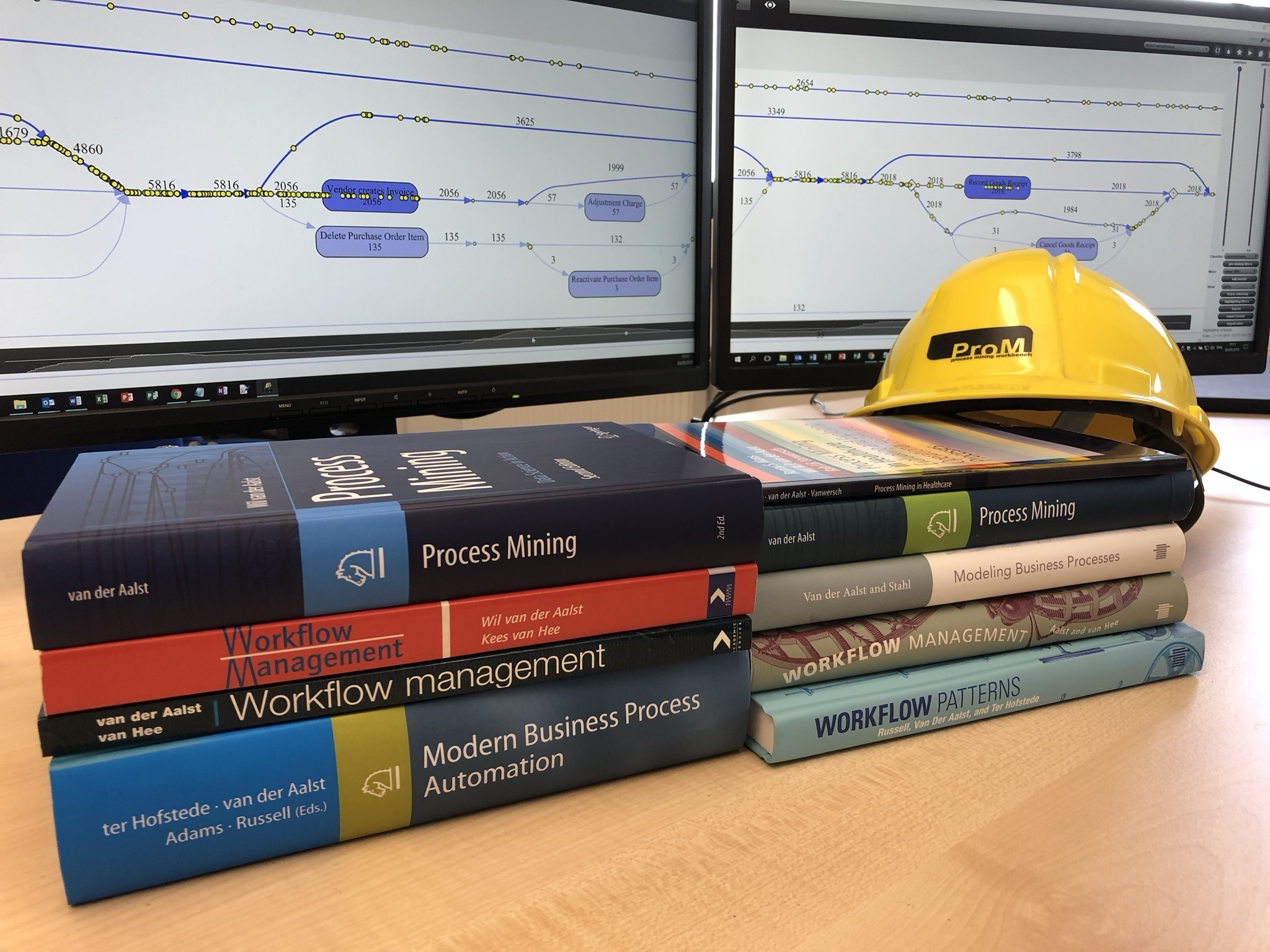 Books about process mining and in the background two monitors