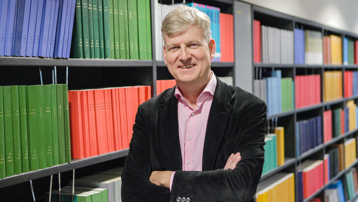 Wil van der Aalst in front of bookshelf